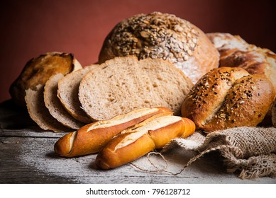 Different kinds of bread and bread rolls on wooden table