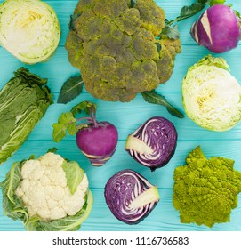 Different kinds of cabbage on a wooden mint color table.
