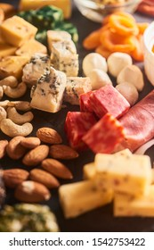 different kinds of cheese, charcuterie assortment, honey, crackers, grapes, nuts and berries close up