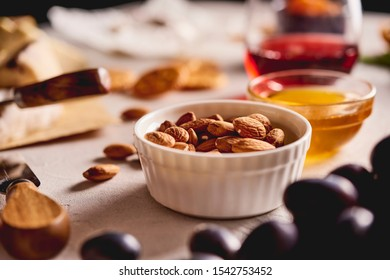 different kinds of cheese, charcuterie assortment, crackers, grapes, nuts and berries on the white concrete background