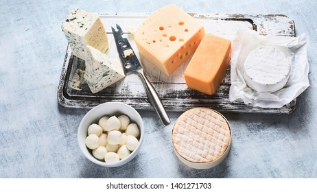 Different kinds of cheeses on wooden board.