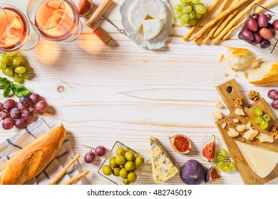 Different kinds of cheeses, wine, baguettes and fruits on white