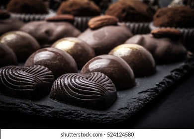 Different kinds of chocolate candies on a slate background. Toned.