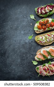 Different kinds of colorful sandwiches on black chalkboard background from above (top view). Party starter or appetizer - flat lay composition with free text space.