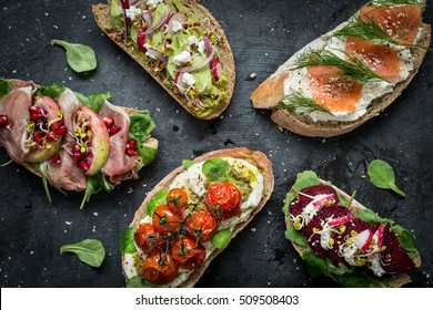 Different kinds of colorful sandwiches on black chalkboard background from above (top view). Party starter or appetizer - flat lay composition.
