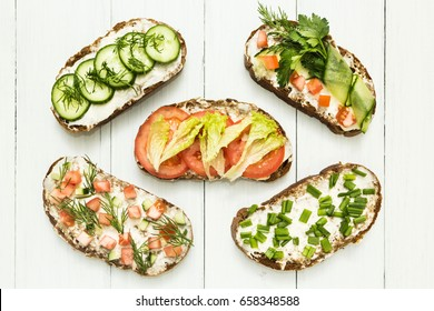Different kinds of colorful sandwiches on white wooden background from above (top view). Party starter or appetizer - flat lay composition.