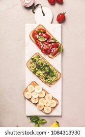 Different kinds of colorful whole grain bread sandwiches on white cutting board over grey concrete background from above (top view). Clean eating, healthy, diet, weight loss food concept