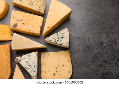 Different kinds of delicious cheese on stone background, top view. Space for text