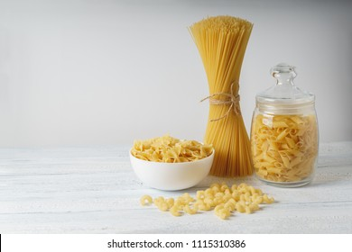 Different kinds of dry pasta and spagetty bunch on white wood table.