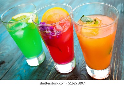 Different kinds of fresh lemonades in glasses on wooden background