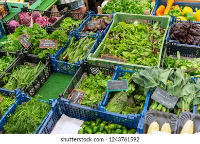 Different kinds of herbs and salad for sale at a market