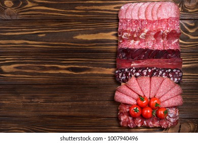 Different kinds of meat cuts on the boards. On a wooden background.