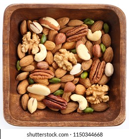 Different kinds of nuts in wooden bowl on a white background. Healthy food.