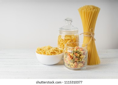 Different kinds of pasta on white wood table.