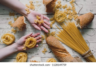 Different kinds of pasta on wooden table, bread, pasta in beautiful girl hands