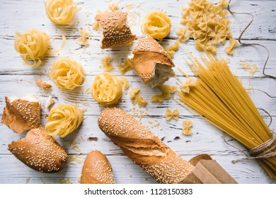 Different kinds of pasta on wooden table, bread