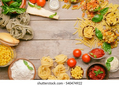 Different kinds of pasta on wooden background
