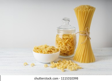 Different kinds of pasta and spagetty bunch on white wood table.