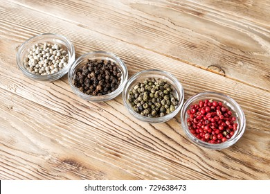 Different kinds of peppercorns. Four variations of peppercorns in glass plates over rustic background. Black, white, green and pink pepper. Dried berries used as spice and seasoning. Food photo.