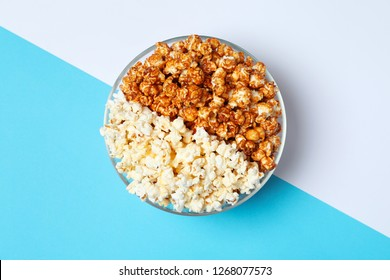 Different kinds of popcorn in bowl on color background, top view