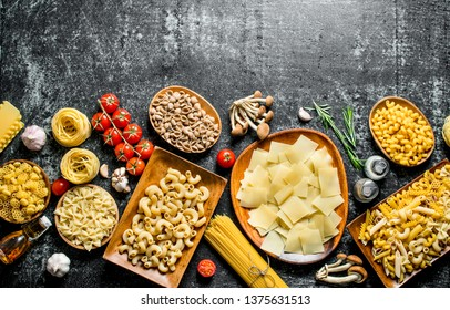 Different kinds of raw pasta with tomatoes and mushrooms. On black rustic background