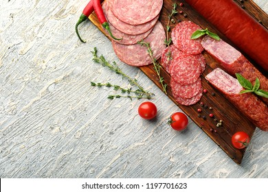 Different kinds of sausages with spices on light table