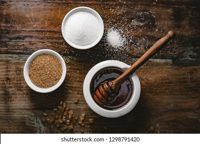 different kinds of sugar and maple syrup on a dark background