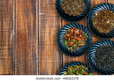 Different kinds of tea on plates on wooden background. Assortment of dry tea. Tea concept. Tea leaves. Top view. Copy space, frame.