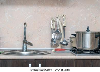 Different Kitchen Utensils - ladle, pan, etc. on the kitchen