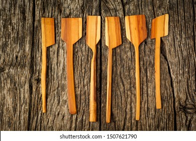different kitchen wooden utensils close up on rustic wooden background.