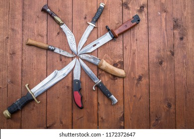 Different knives laying in a circle on a table.