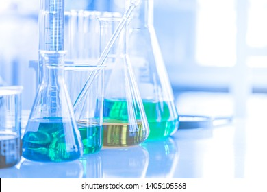 Different laboratory glassware with color liquid and with reflection. Tube, flask and beaker
