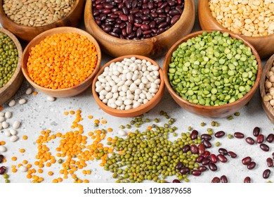 Different legumes. Mung, red and white beans, lentils, peas and chickpeas in wooden bowls on the light grey kitchen table.  Vegetarian food
