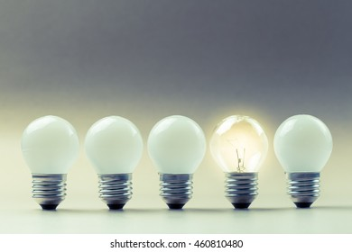 Different light bulb glowing in the row
