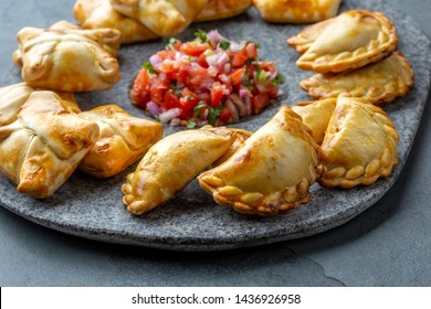 Different little cocktail EMPANADAS on stone plate with tomato sauce and guacamole . Gray background. Latin American and Spanish tipical food