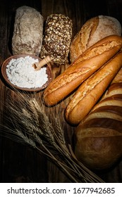 Different loaves of tasty bread with wheat, flour and gluten on a wooden table