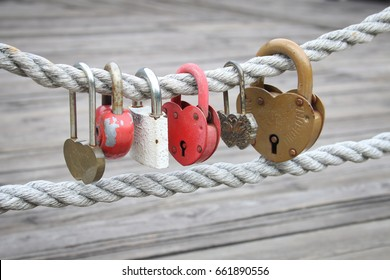 "lot of different love padlocks on thick hemp rope. the inscription on the lock ""advice and love"". not brand"