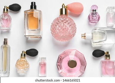 Different luxury perfume bottles on white background, top view
