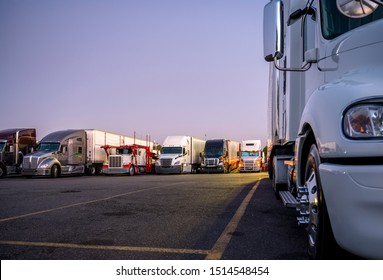 Different make and models big rigs semi trucks with semi trailers standing in row on truck stop parking lot for rest and comply with the movement according to the schedule for successful delivery