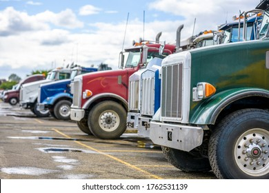 Different makes, models and colors big rigs tipper industrial freight semi trucks tractors standing in row on the warehouse parking lot waiting for next loads for delivery