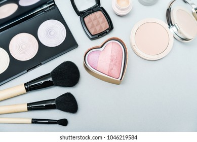 Different makeup brushes and cosmetics on light blue background, top view