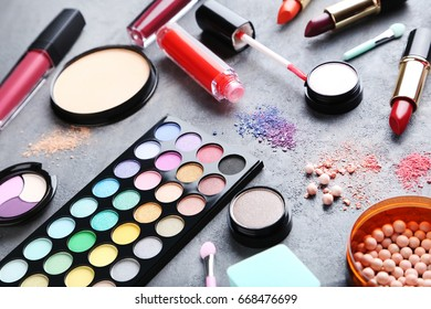 Different makeup cosmetics on grey wooden table