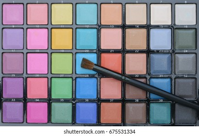 Different makeup cosmetics on rustic white wooden table.