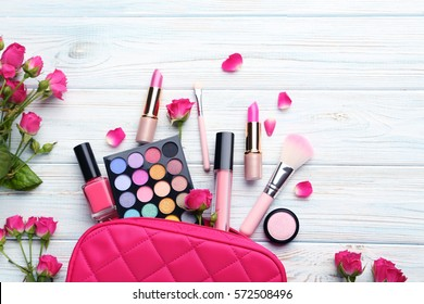 Different makeup cosmetics on white wooden table