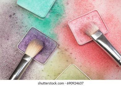 Different make-up palettes and brushes on white