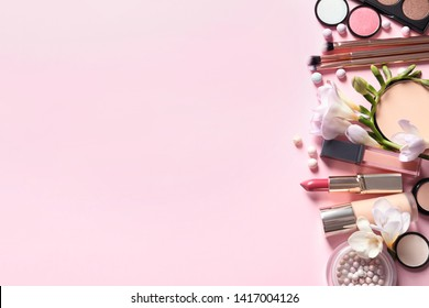 Different makeup products with flowers on color background. Space for text