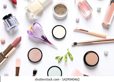 Different makeup products and flowers on white background, top view