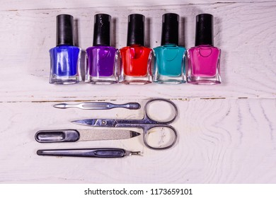Different manicure tools and nail polishes on rustic wooden table. Top view