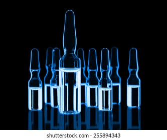 Different medical ampules toned blue on black background