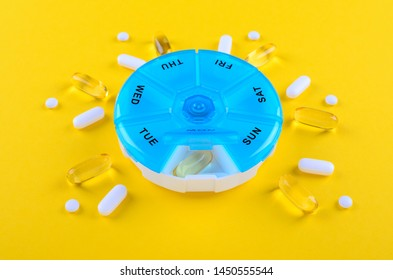 different medicines, omega capsules, for one week and a blue pills box on yellow background